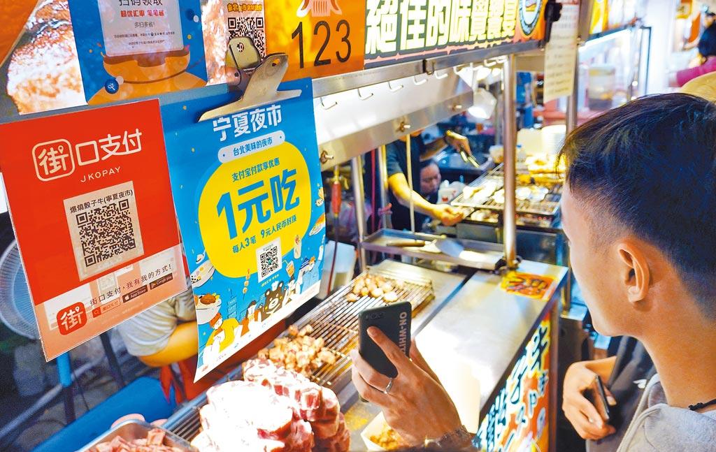 台北寧夏夜市許多攤商上都接受「街口支付」、「支付寶」等行動支付方式,供消費者刷手機付款。(姚志平攝)