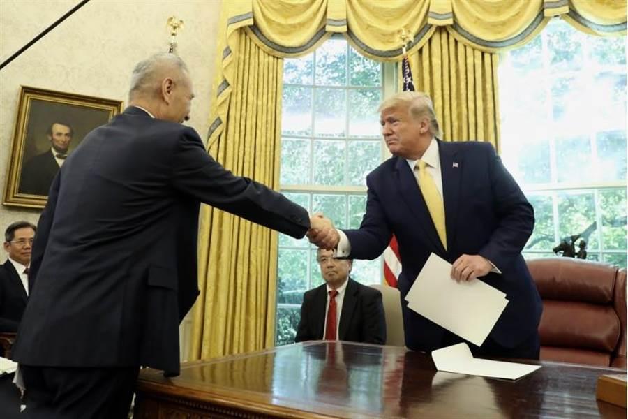 美國總統川普與中國大陸副總理劉鶴在美國白宮橢圓形辦公室握手。(圖/美聯社)