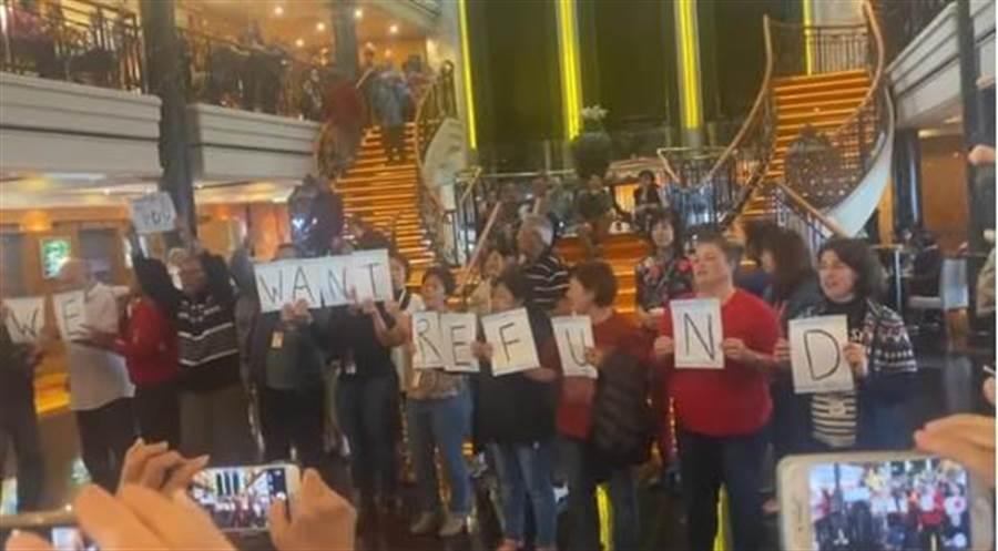 旅客們憤怒的在郵輪大廳抗議,要求下船跟退款。(照片翻攝自YouTube)