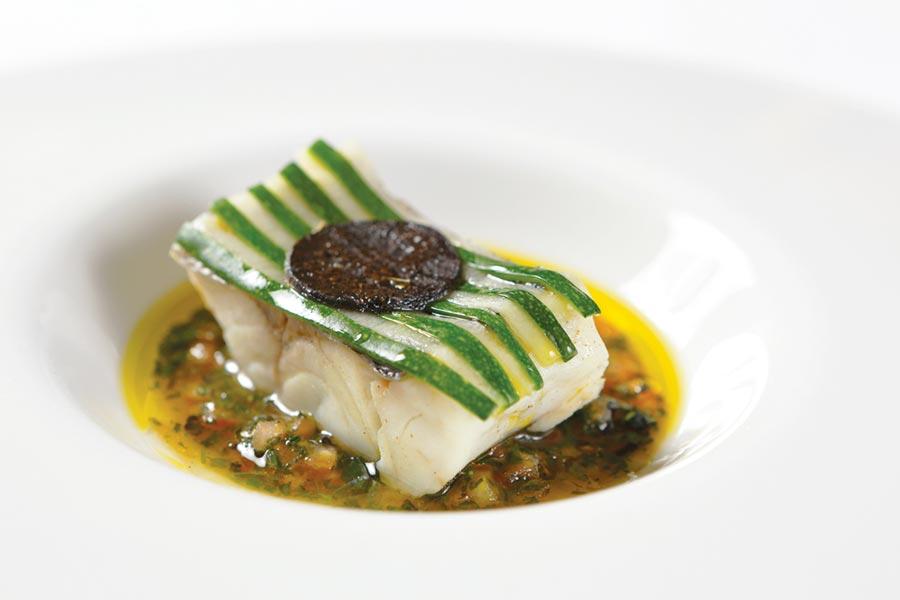 〈露西松露香草狼鱸〉低溫烹調的海鱸魚有果凍般的口感,鋪在上方的櫛瓜 和黃瓜片必須一條條裁切擺放,非常費工。圖/Thomas Chien法式餐廳