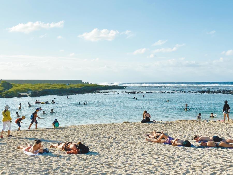 大量遊客國慶連假湧入綠島,沙灘上隨處可見遊客戲水享受日光浴。(楊漢聲攝)