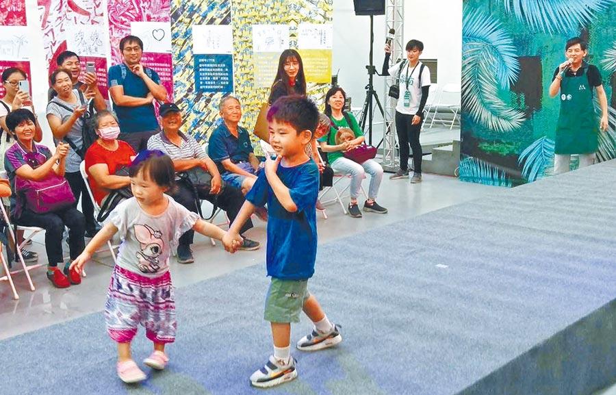 藝人黃子佼11日到台灣設計展擔任一日店長,在「超級狂伸展台」邀小朋友上台走秀,並與民眾開心合照。(潘建志攝)