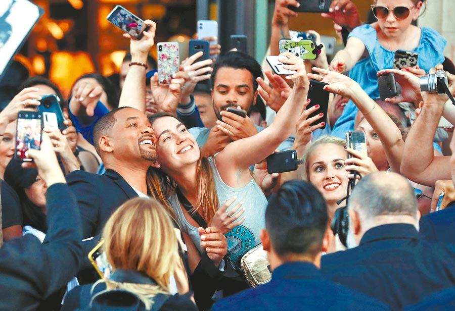 威爾史密斯(左)深知社群媒體力量,在加州宣傳時不放棄與任何一位粉絲拍照。(路透)