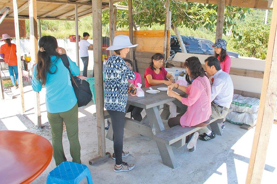 自由行陸客在花蓮海岸路邊攤吃烤飛魚。(記者李鋅銅攝)