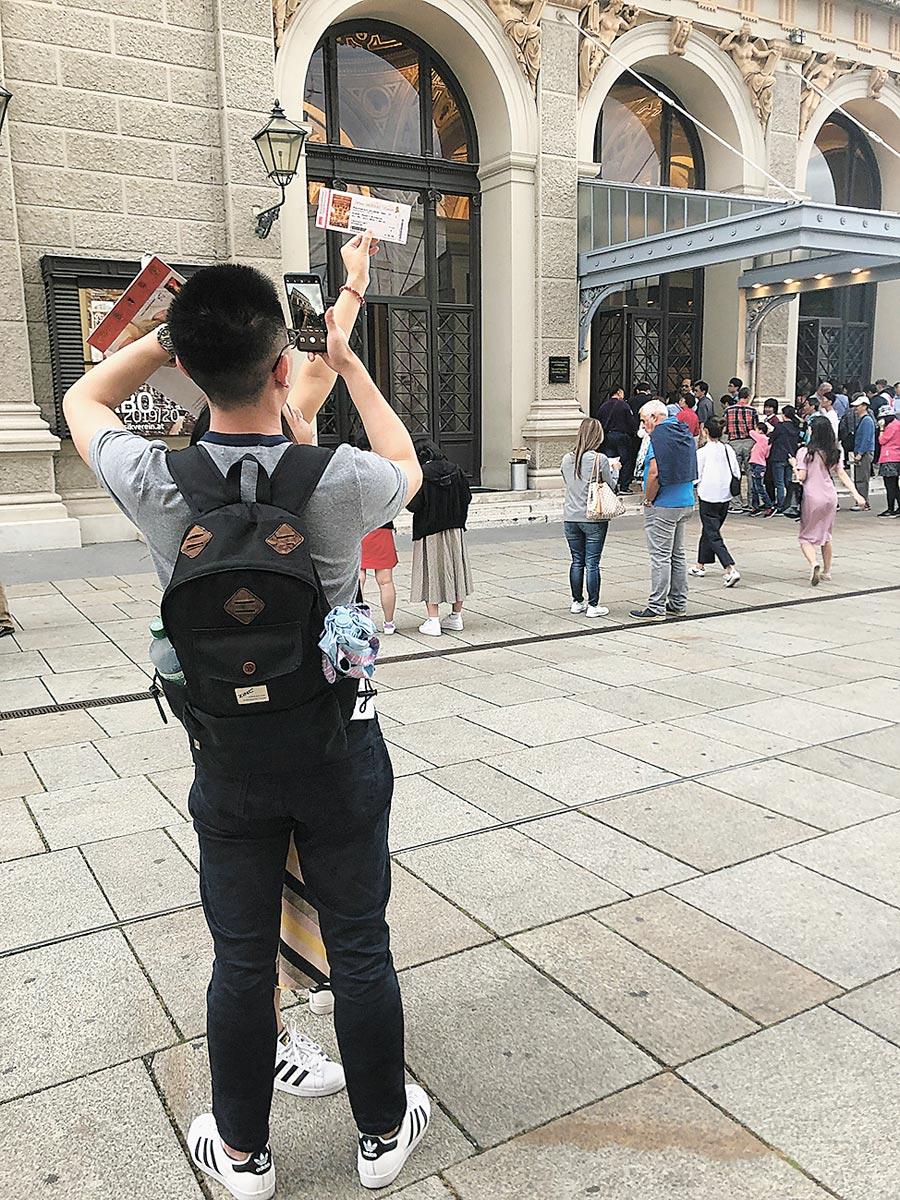 拿著維也納金色大廳門票,陸客在金色大廳外拍照留念。(記者李鋅銅攝)