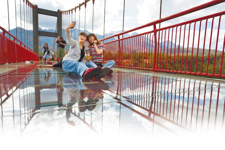 遊客在麗江東巴秘境景區內的「東巴秘境玻璃棧道」留影。(新華社資料照片)