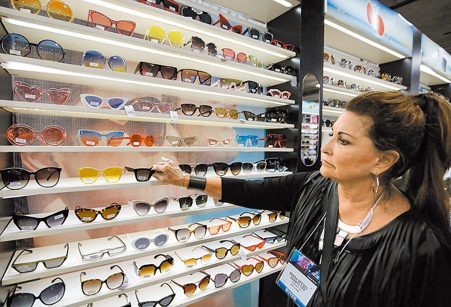 劉鶴指出,貿易戰下,企業和消費者都會受到極大損失。圖為8月11日,拉斯維加斯一名採購商在「折扣商品展」上選購中國製造的墨鏡。(新華社)
