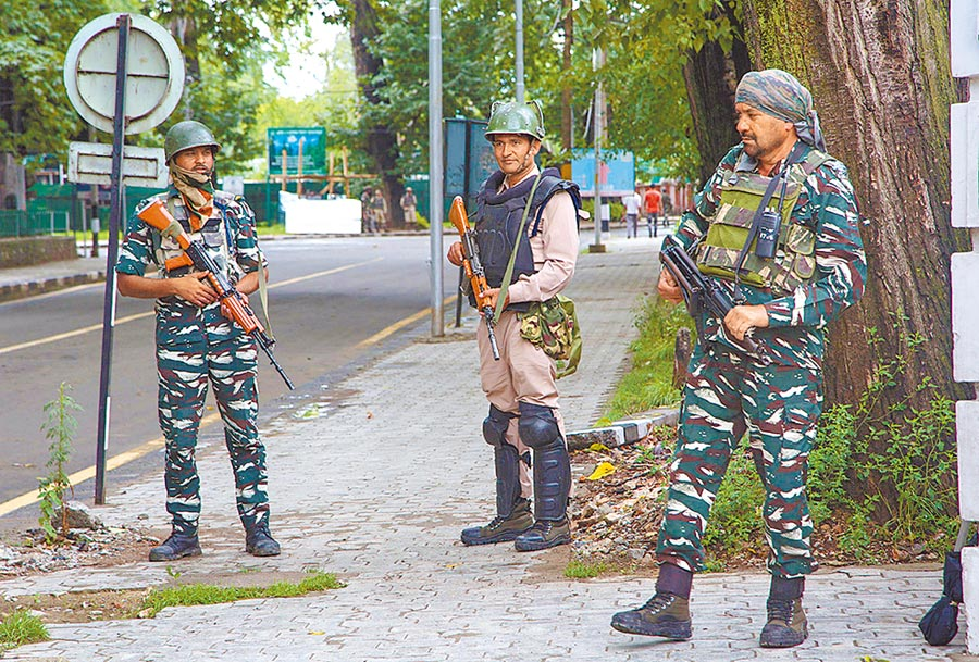 8月14日,在印控喀什米爾首府斯利那加,印度士兵在街頭檢查站執勤。(新華社)