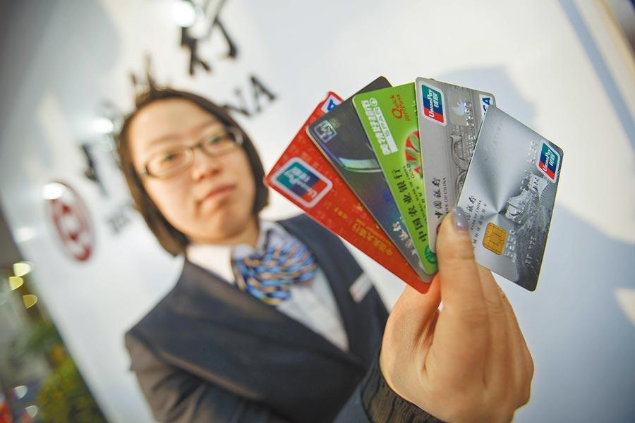 銀行工作人員展示信用卡。(中新社資料照片)