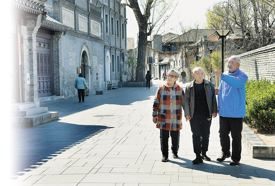中醫的六經舒膚操老少皆宜,圖為4月2日北京前門東區,老人們正在散步。(新華社)