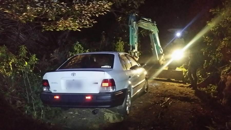 挖土機將汽車輪胎吊起後,順利協助該對情侶脫困。(翻攝照片/巫靜婷苗栗傳真)