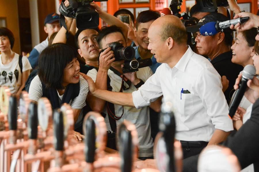 高雄市長韓國瑜14日下午參觀駁二藝文特區,在大義區C11倉庫的細酌牛飲餐酒館裡,一名熱情支持者特別上前要他加油。(林宏聰攝)