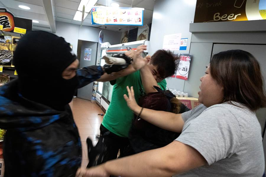 穿著綠色上衣的香港市民遭到著黑衣的示威者圍毆,滿臉是血躲入商店求救,一名婦女試圖阻止他們繼續行使暴力。(圖/路透)