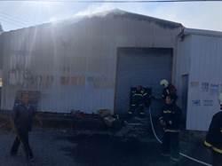 鐵皮屋冒濃煙 消防員切割鐵門滅火