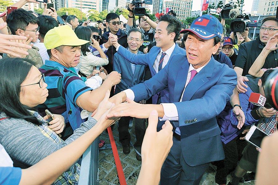 郭台銘(右)初選敗選後,選擇退黨,帶走支持者,每天花樣百出,招招都在打擊國民黨。(本報資料照片)
