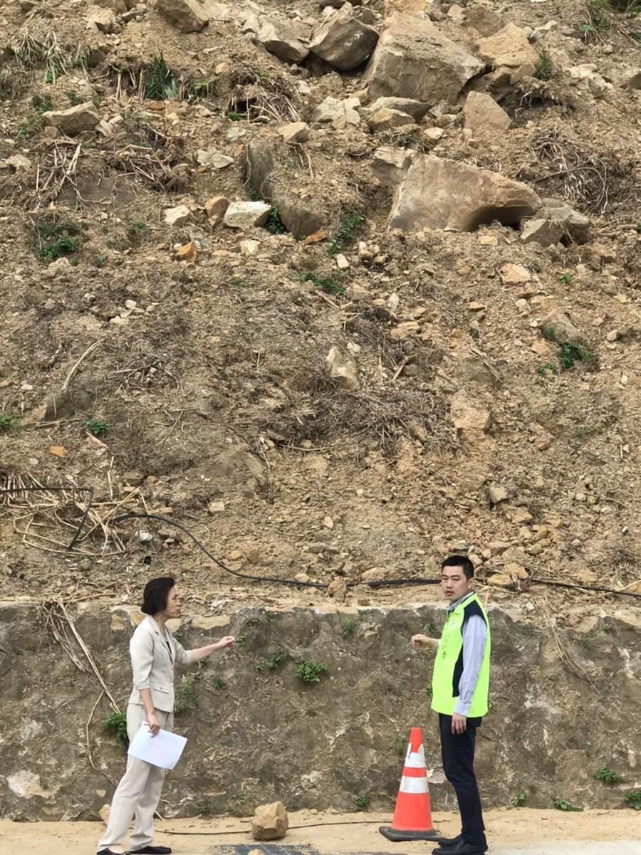萬里野柳隧道旁邊坡因颱風米塔導致坍方,至今仍有多顆巨石佈滿山波,新北市議員張錦豪(右一)與萬里區長粘雪琴(左一)在坍方路段討論後續整修工程。(新北市議員張錦豪提供/張睿廷新北傳真)