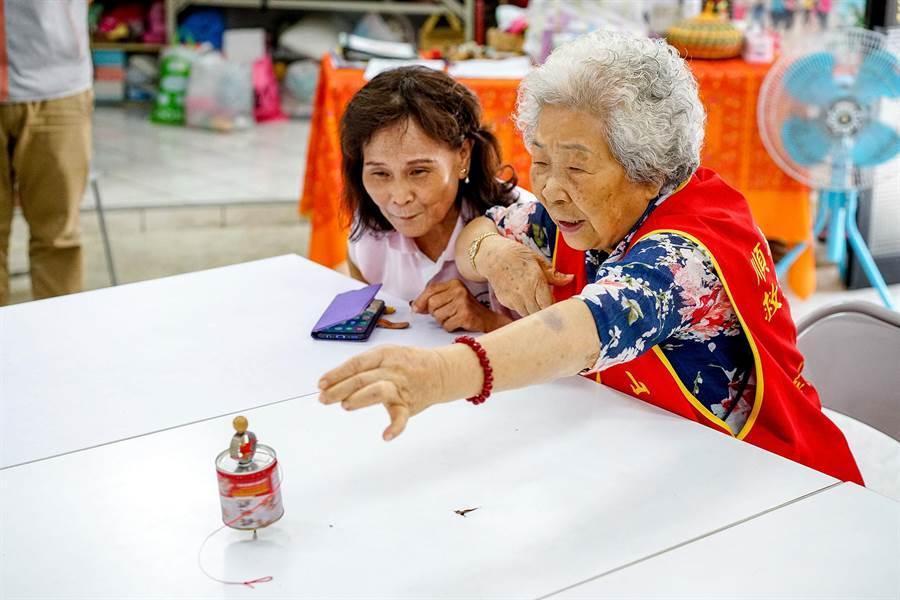 華山基金會羅東愛心天使站今天邀請服務的長者,在漢民社區志工的陪伴下回味古早童玩。(李忠一攝)