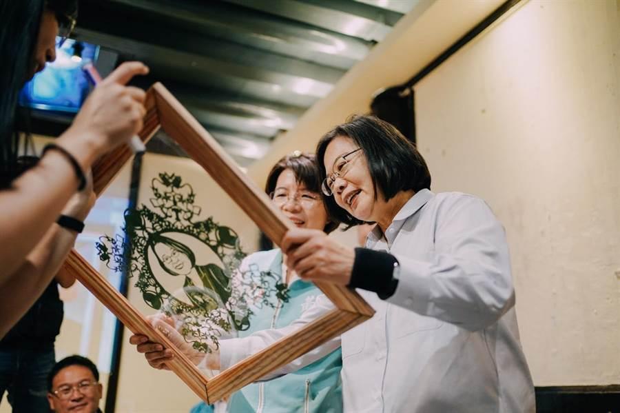 彰化在地青年、文創工作者林昱君送上自己親手剪的小英肖像窗花紙,蔡英文總統仔細端詳。(黃秀芳服務處提供/謝瓊雲彰化傳真)