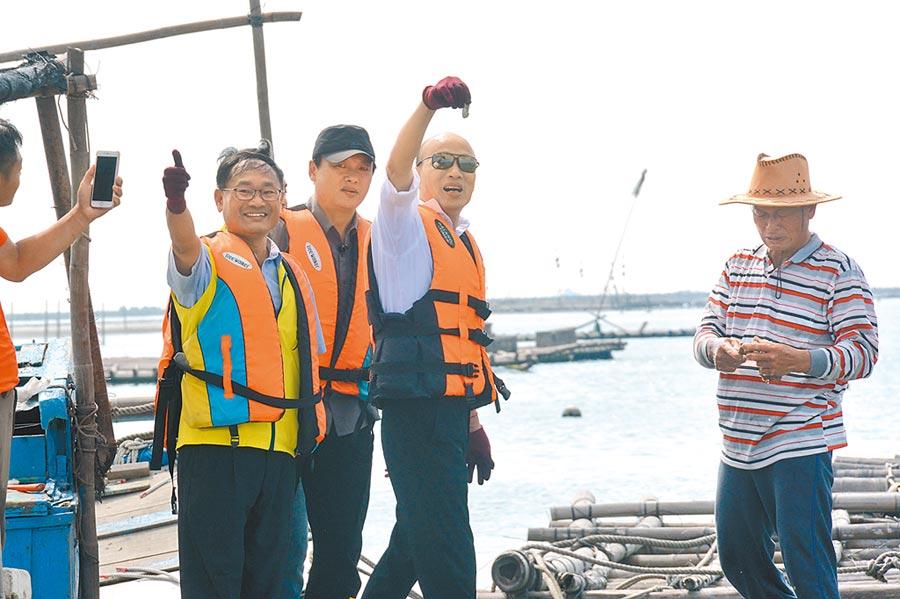 韓國瑜(右二)22日在嘉義東石體驗採蚵樂;蚵農當場採鮮蚵給他,不過韓僅高舉給媒體拍攝,並沒有吃下肚。(林宏聰攝)
