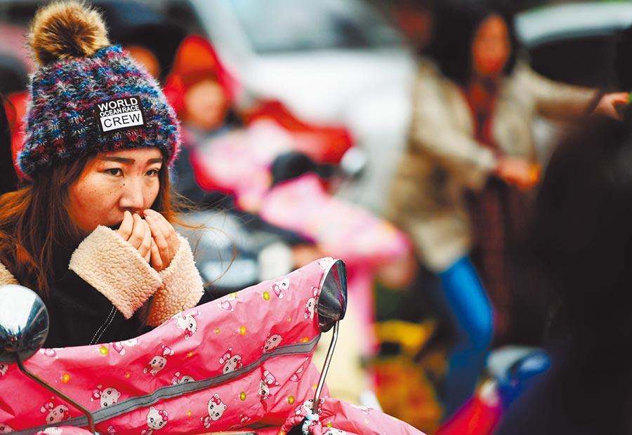 大陸一名女子在寒冬中暖手。(中新社資料照片)