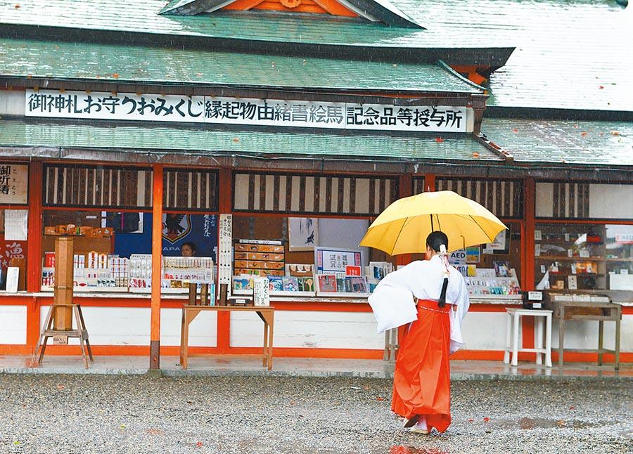 日本和歌山縣的熊野那智大社,神社的一名巫女在雨中行走。(新華社資料照片)