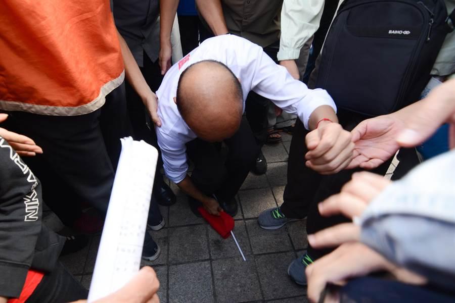 有支持者手持的小國旗在推擠時不慎掉落,韓國瑜立刻彎腰撿起。(林宏聰攝)