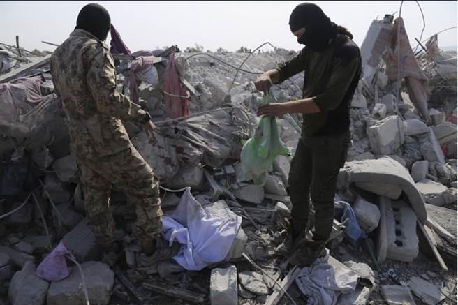 美軍26日鎖定伊斯蘭國(ISIS)最高領袖巴格達迪,突襲敘利亞西北部土敘交界附近小村巴里沙(Barisha)後,民眾27日看著滿目瘡痍的景象。(美聯社)