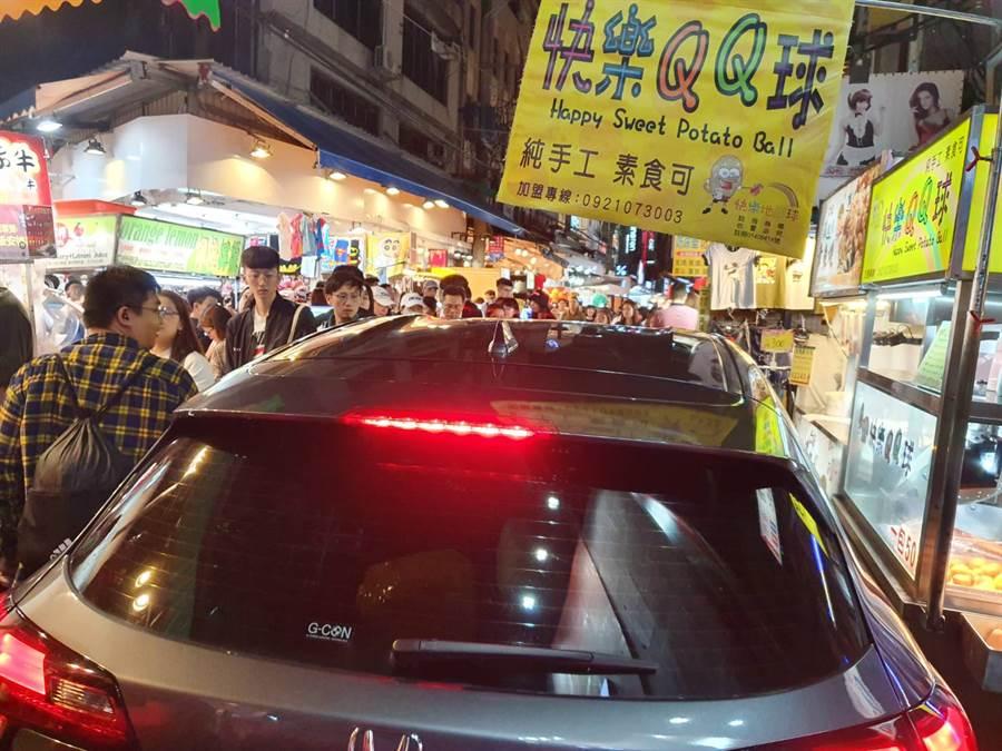 士林夜市假日人潮擠得水洩,有駕駛將車開進夜市路中間。(照片/《我是北投人》粉絲團 授權提供)