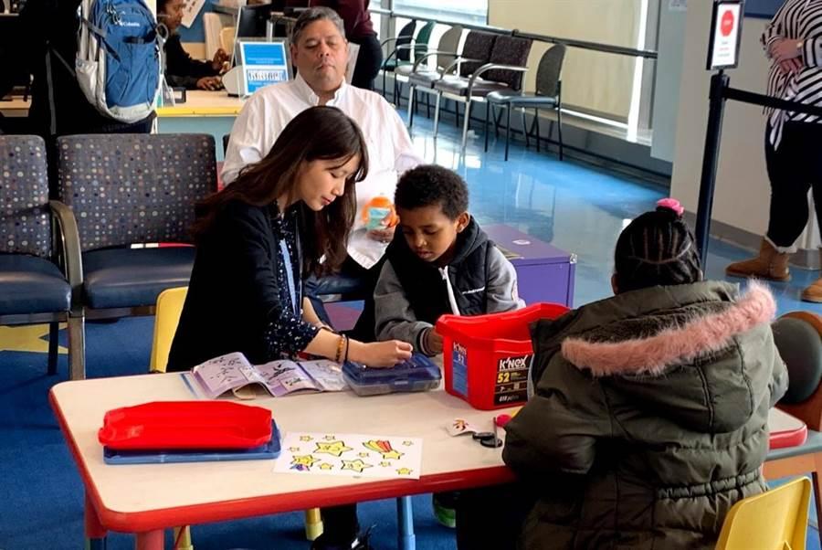 幼兒園教師楊雅涵前往美國波士頓醫學中心擔任幼兒門診志工,在候診間陪伴孩子看童書、玩遊戲,緩解看病的焦慮。(教育部提供/林志成台北傳真)