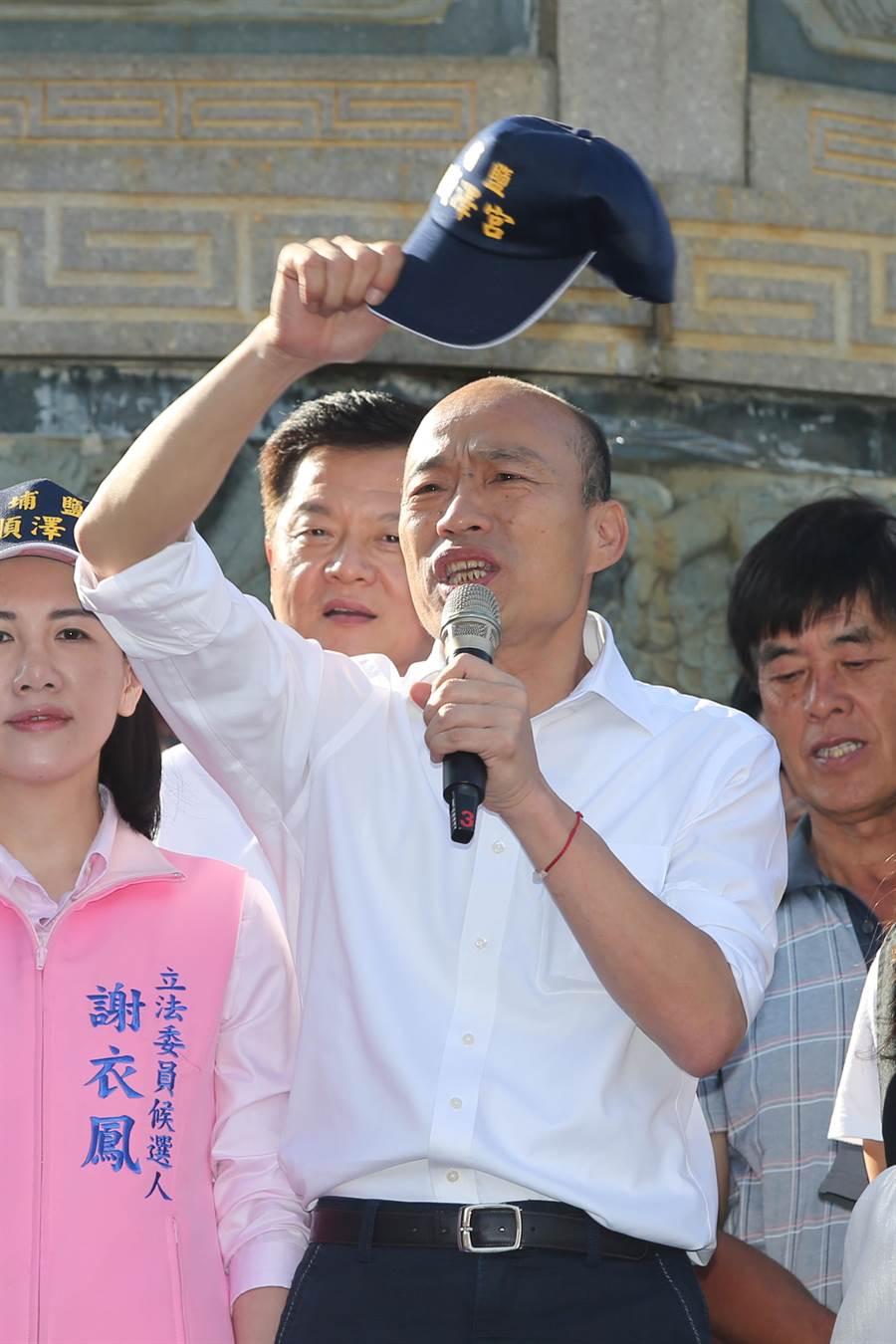 韓國瑜揮舞順澤宮的冠軍宮廟帽向現場支持者發表談話。(黃國峰攝)