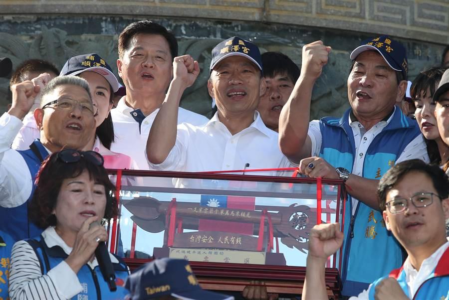頭戴順澤宮廟帽的韓國瑜(中)收下埔鹽鄉代會主席陳武騰(右)送的一隻穿雲箭。(黃國峰攝)