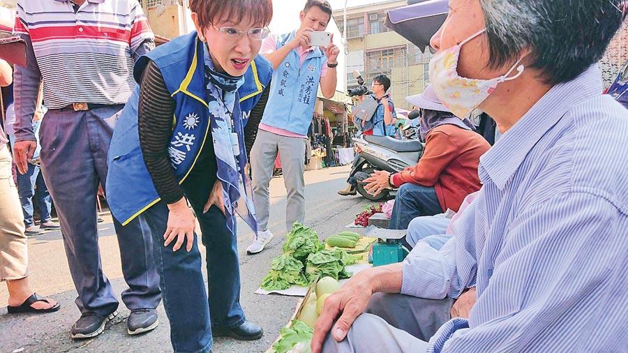 前國民黨主席洪秀柱(藍領黃邊者)在菜市場與菜販們聊天話家常。(程炳璋攝)