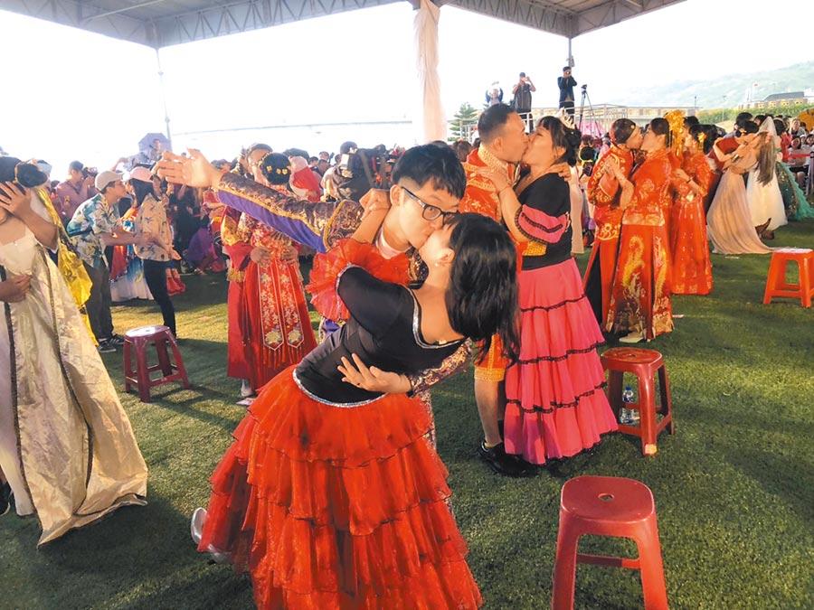 新北市聯合婚禮的100對新人們穿上各國婚禮服飾,並激吻99秒,有人吻到撲倒在地上,讓市長侯友宜、副市長謝政達及眾人都笑成一片。(吳康瑋攝)