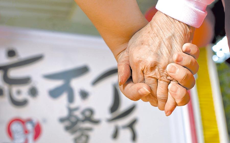 志工與老人的牽手,讓她們「忘不了」。(曹彤攝)