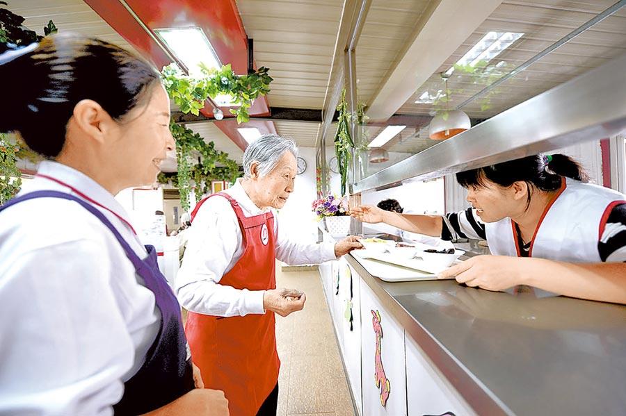 工作人員引導老人為顧客上菜。(曹彤攝)
