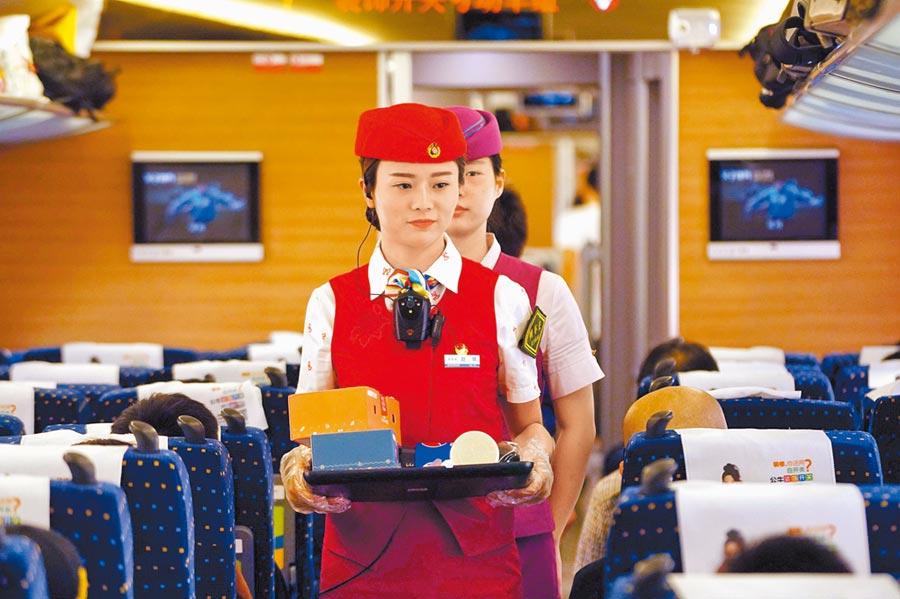 武漢鐵路局武漢客運段列車工作人員為旅客配送餐食。(新華社資料照片)