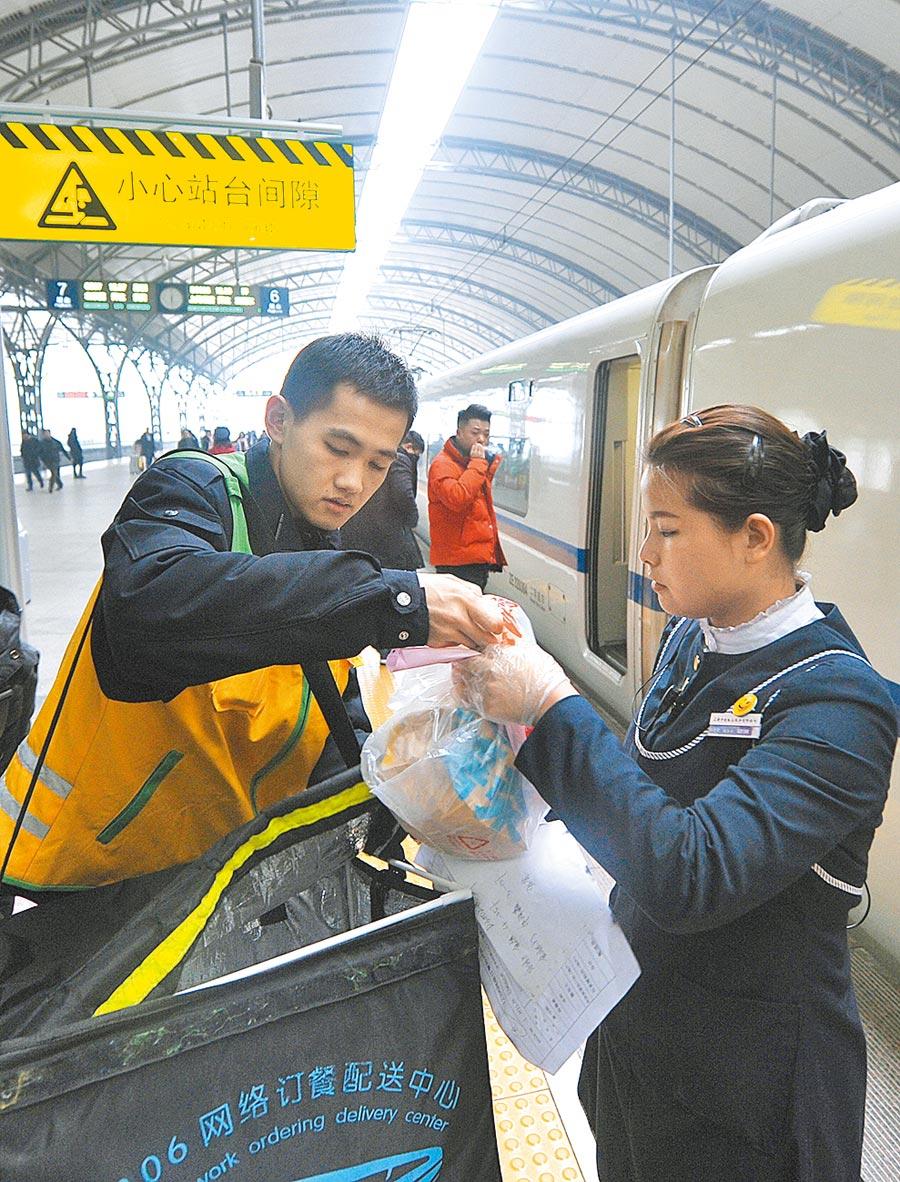 漢口站是接受互聯網訂餐的車站之一,高鐵外賣小哥將外賣交到列車工作人員手中。(新華社資料照片)
