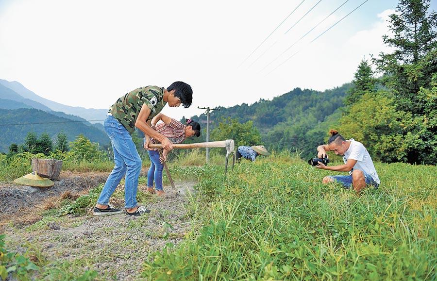 9月22日,鄉村「網紅」忙「豐收」,網路達人在湖南省鄉村一塊花生地裡錄製影片。(新華社)