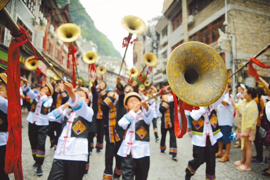 6月15日,貴州鎮遠古城街道上吹嗩吶巡遊。當日,當地舉辦非遺展演等豐富多彩的民俗活動。(新華社)