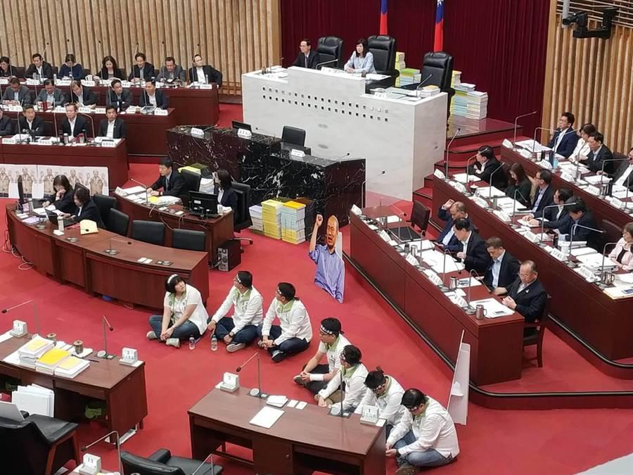 對於高雄巿議會藍綠流血衝突,民進黨議員1日集體綁黑布條靜坐抗議。(曹明正攝)