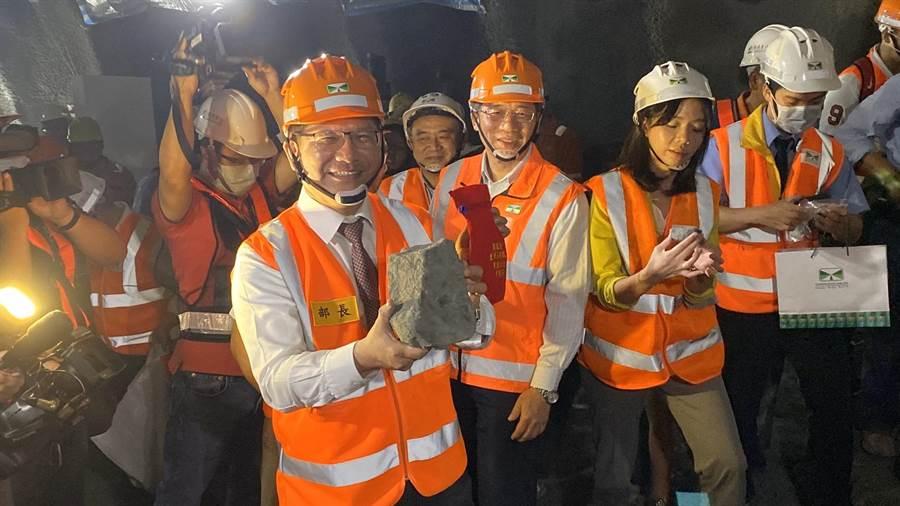 交通部長林佳龍撿起一大顆貫通石留念。(王文吉攝)