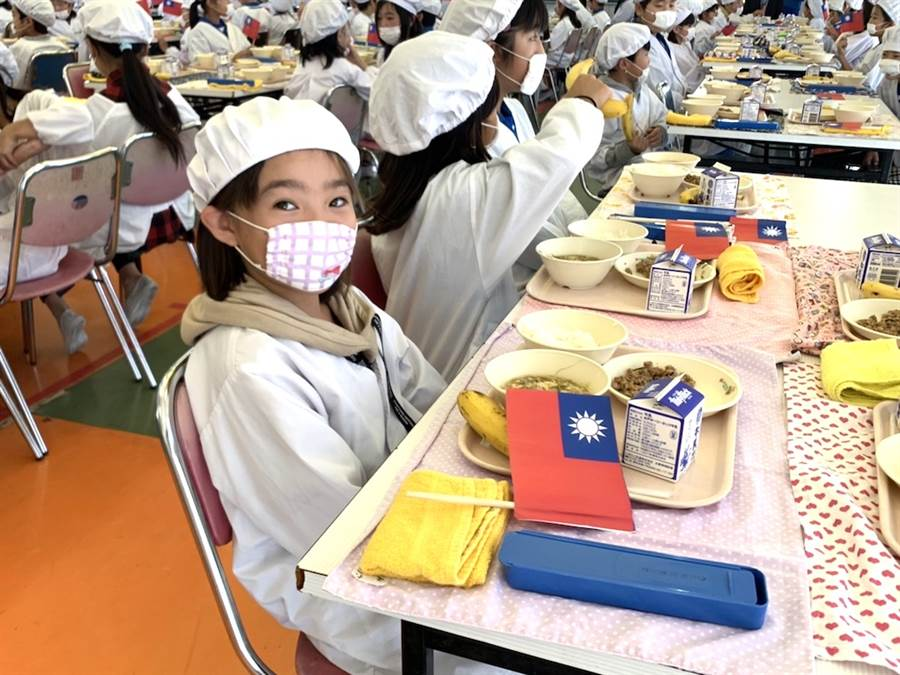 日本笠間市稻田小學學童1日的營養午餐是台灣「滷肉飯」及「秋冬香蕉」,桌上還放著中華民國國旗。(黃菁菁攝)