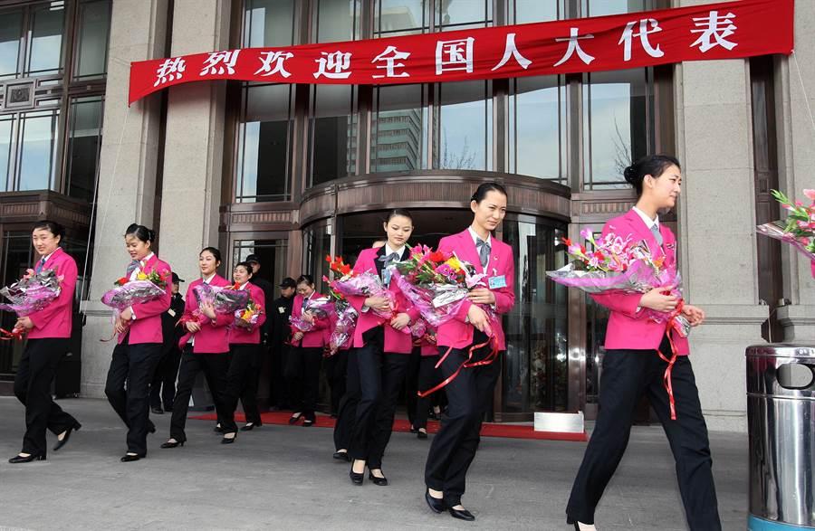 圖為2008年大陸全國人大一次會議各省代表團入駐京西賓館,賓館服務員手捧鮮花列隊迎接。(圖/中新社)