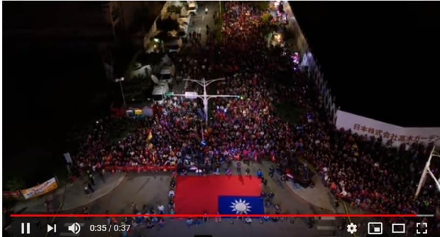 韓國瑜桃園傾聽之旅最終場,地點在桃園經國重劃區,滿滿的人潮前有一面大國旗。(翻攝「Johnny Lin空拍」YouTube)