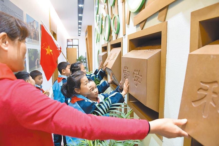 10月31日,志願者給浙江湖州市的八里店鎮常路學校小學生講解社會主義核心價值觀。(新華社)