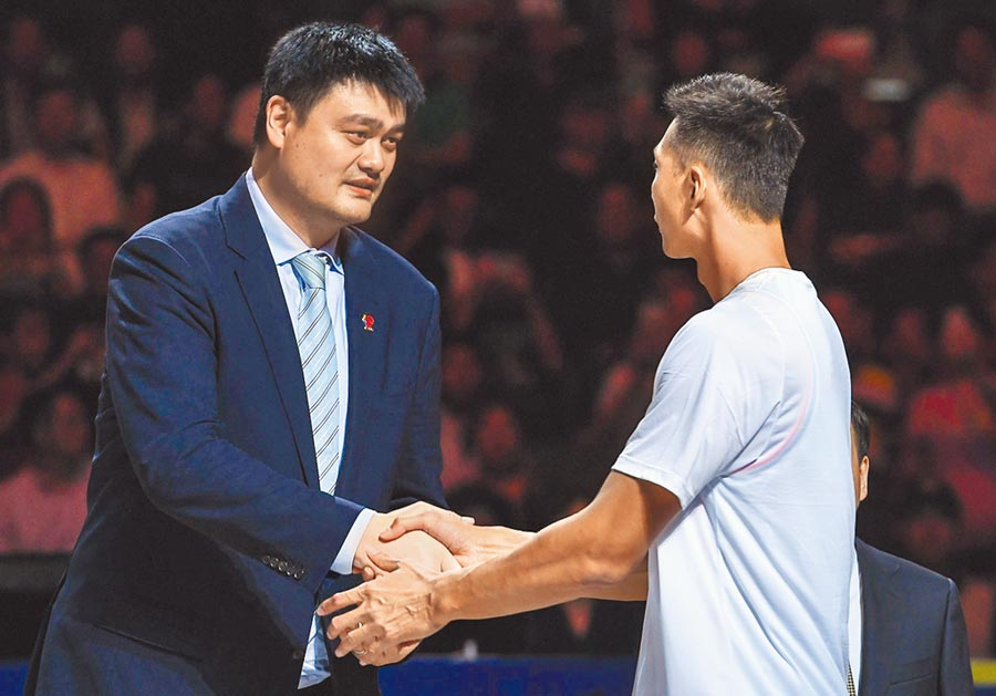 11月1日,中國籃球協會主席、CBA公司董事長姚明(左)在儀式上與廣東東莞銀行隊球員易建聯握手。(新華社)
