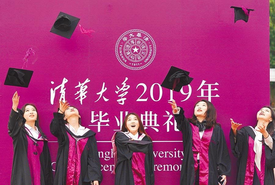 7月7日,北京清華大學畢業生在合影時拋起學士帽。(新華社)