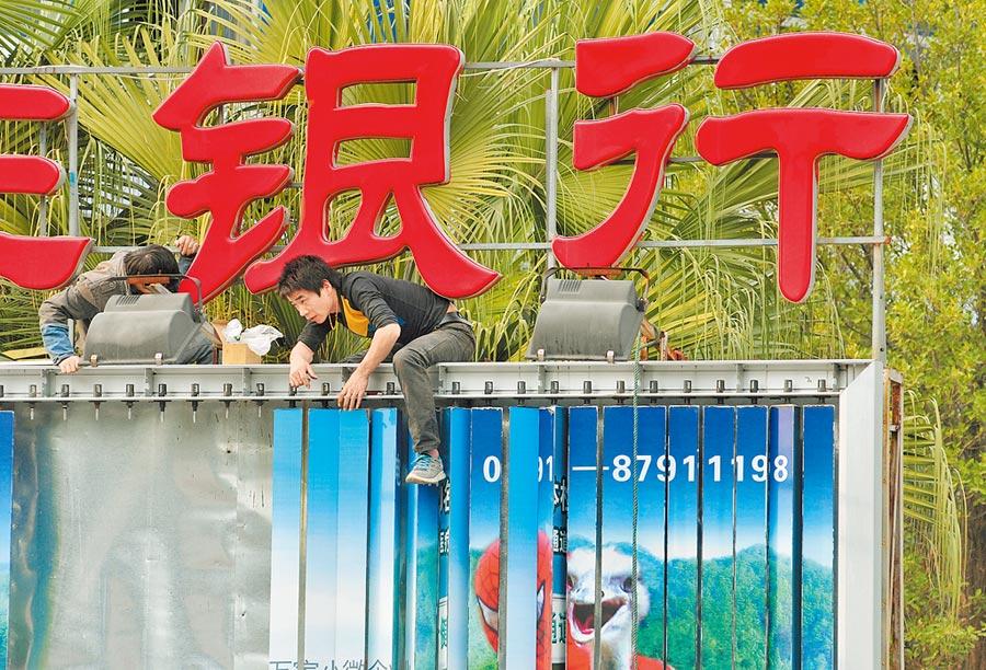 重慶農商銀行股價險破淨值,顯示大陸農商行出現警訊。圖為福州工人在為銀行更換廣告牌。(中新社資料照片)