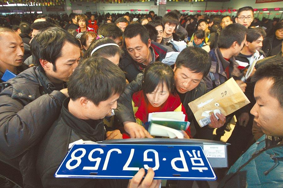 北京南四環花鄉汽車交易市場,人們在取號機前爭相取號。(CFP)