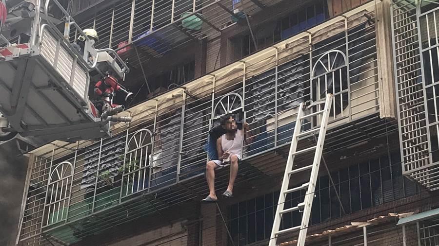 40多歲的外籍人士坐在陽台待援。(戴上容攝)
